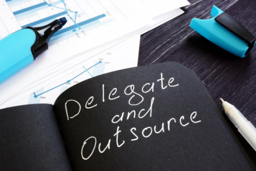 Black paper with delegate and outsource written down